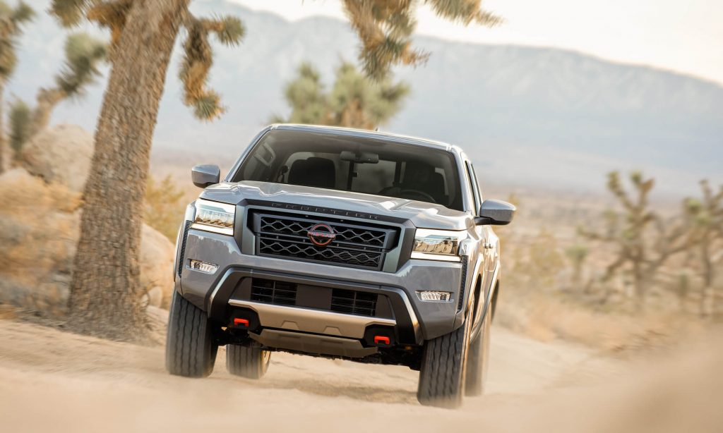 The 2022 Nissan Frontier driving toward the viewer on a dusty road.